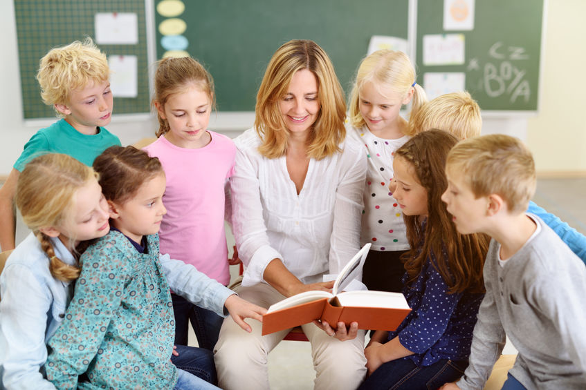 Female Teacher Reading a Story From the Book to her Little Young Students Inside the Classroom